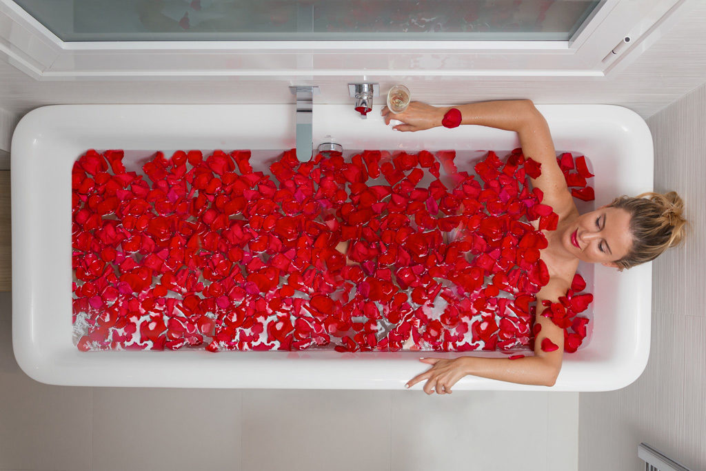 A bathtub with rose petals for a romantic weekend break
